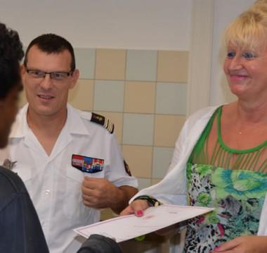 La directrice de la DPJEJ et le directeur du CSN remettent son certificat à l'un des sept mineurs.