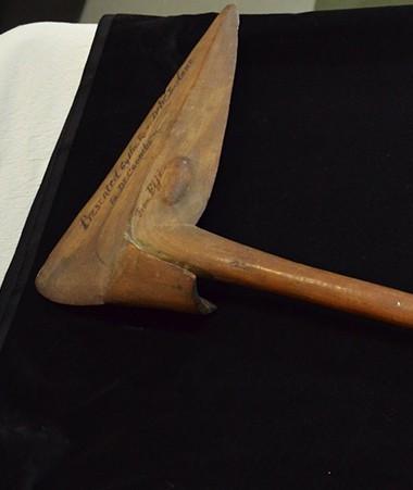 La massue bec d'oiseau, en excellent état, présente un magnifique tressage de poils de roussette. À ses côtés, un portrait du révérend Samuel MacFarlane.