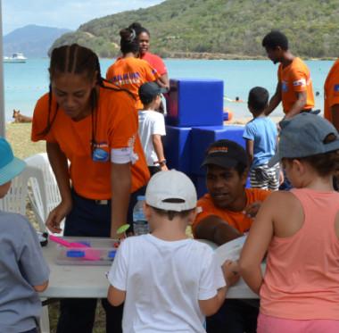 De jeunes auxiliaires de sécurité civile expliquent à des enfants la formation d'un tsunami… en modèle réduit.