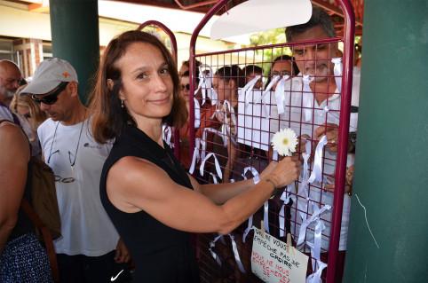 À l'issue du rassemblement, les participants, comme ici Isabelle Champmoreau, ont attaché des rubans blancs et des fleurs sur des grilles, en signe de solidarité.