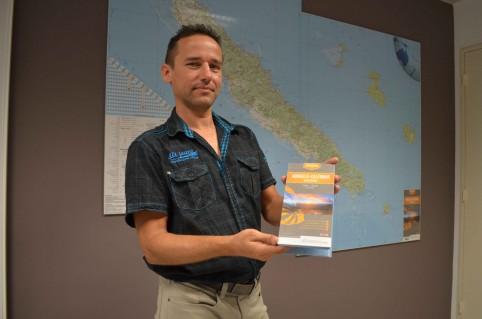 Clifford Delathière, chef du bureau de la cartographie de la DITTT. Derrière lui, le poster agrandi au 1/250 000e, en deux parties.