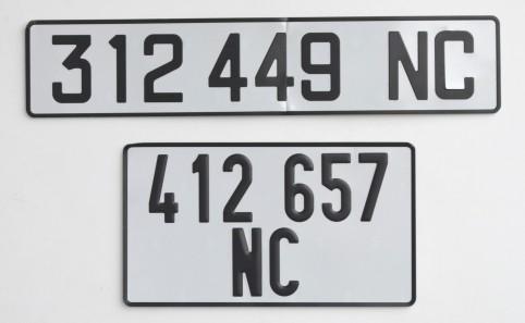 Des caractères bâton noirs pour les chiffres et les lettres. Et un fond tout blanc et rétro-réfléchissant.