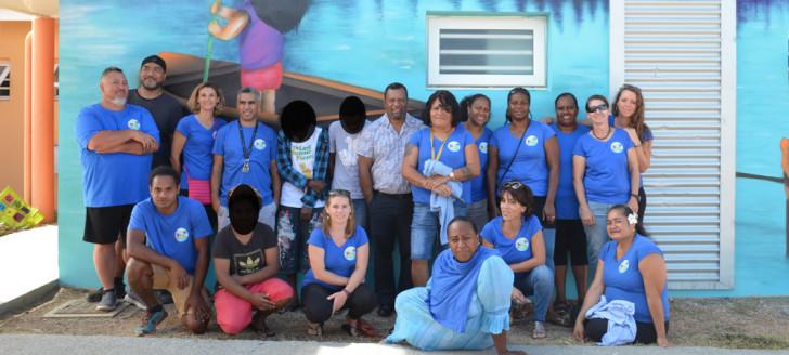 Didier Poidyaliwane et l'équipe du FAEN, dont sa directrice Karen Vernière (1er rang, 2e à droite), devant la fresque réalisée par les jeunes à l'occasion de l'anniversaire du foyer.